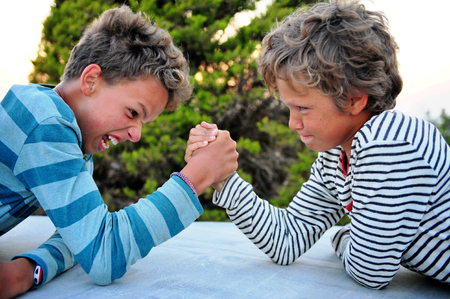 Two brothers playing armwrestling outdoors 写真素材