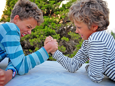 Two kids playing armwrestling in the park