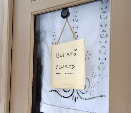 Closed sign in english and greek languages in the store