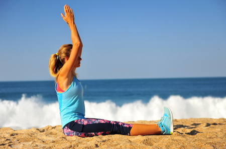 Blond woman siting on beach with hands in the air