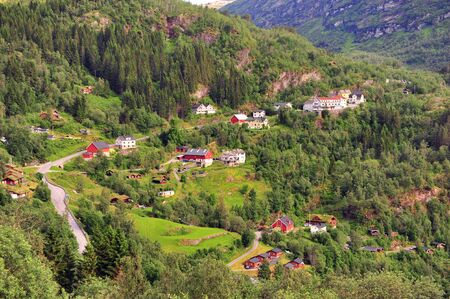 Green hills with traditional houses in Geiranger, Norway