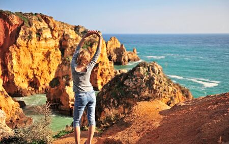 Young woman at sea cliffs in Lagos, Portugal