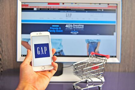 Yaroslavl, Russia - August 14, 2019: Hand holding mobile phone with Gap logo and retailer's website on background on August 14, 2019. Editorial