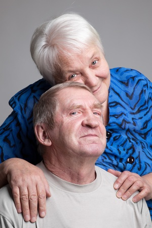 A loving, handsome senior couple on a grey background Stock Photo