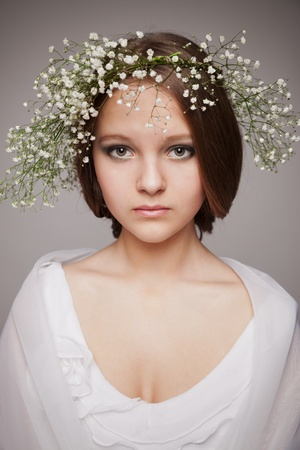 portrait of beautiful healthy teen girl with wreath of flowers, on grey photo