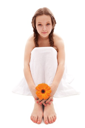 young woman hand and feet with manicure and orange flower isolated on white photo