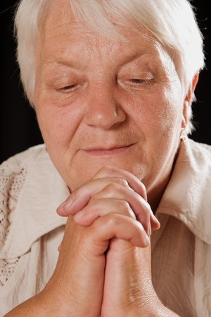 The elderly woman meditation on a black background photo