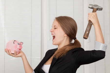 girl  about to break his piggy bank with hammer