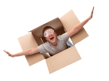 boy in a cardboard box dreams that it flies in an airplane on the sky