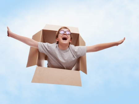 The boy in a cardboard box dreams that it flies in an airplane on the sky Stock Photo - 15063764
