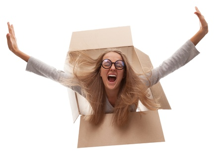 The girl in a cardboard box flies in white background Stock Photo