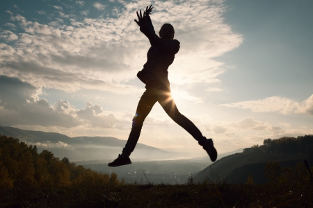 Happy young woman jumping at the sunset  photo