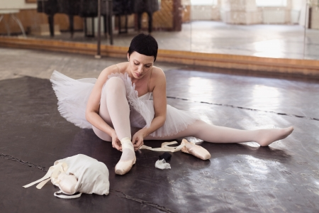 ballerina puts on pointes sitting on a floor in a ballet hall