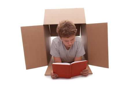cramped space: boy has retired to a cardboard box  Stock Photo