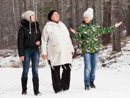 Senior  woman walks on winter wood with  girl and boy Stock Photo