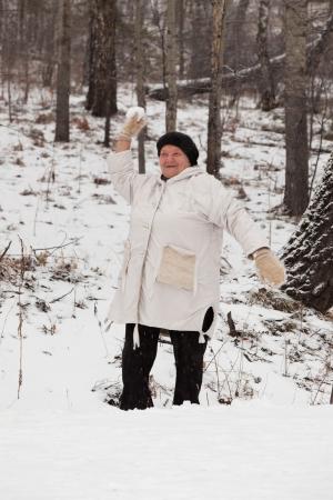 Starší žena procházky a hrát sněhové koule Reklamní fotografie
