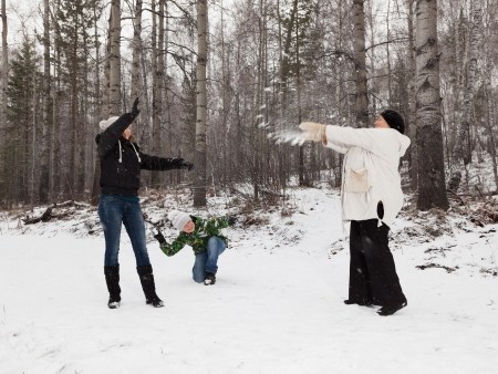 Senior  woman ,  girl and boy play snowballs  photo