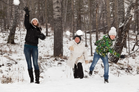 Senior  woman ,  girl and boy play snowballs
