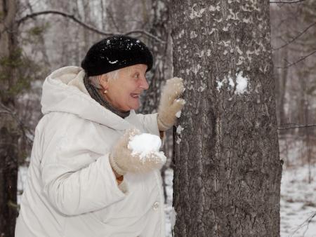 Senior  woman walks and  play snowballs