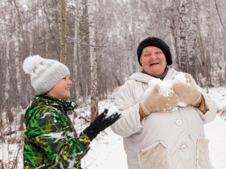 Senior žena a chlapec hra sněhové koule