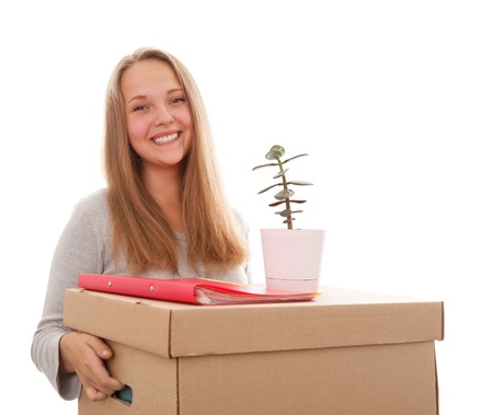 belongings: The girl smiles and has control over a box with a house flower on a white background Stock Photo