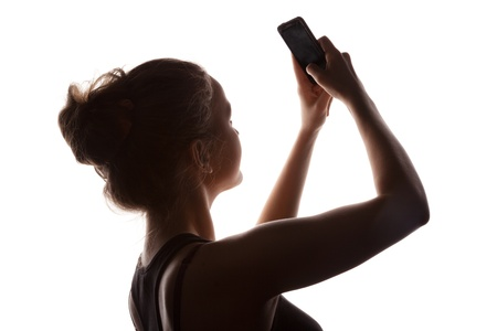 profile young woman in a shade of a silhouette with phone isolated on a white
