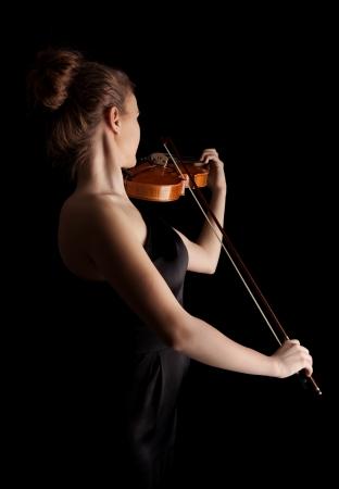 Mladá žena hrát na housle na černém pozadí Reklamní fotografie
