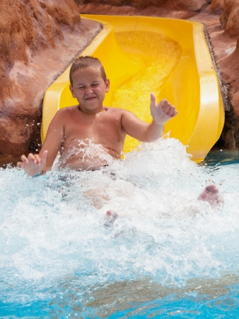 boy on water slide at aquapark  Summer holiday