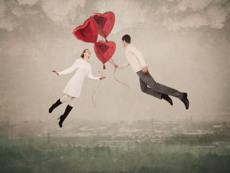 The young woman and the man flying by a balloon in the form of heart Banque d'images