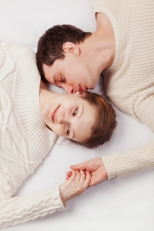 girl and the young man in white knitted jackets lie on a sofa Banque d'images