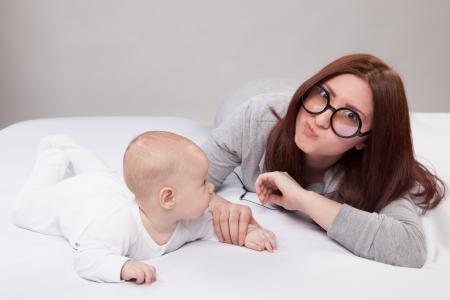 Fille se trouve sur un canapé blanc avec le bébé Banque d'images - 18872102