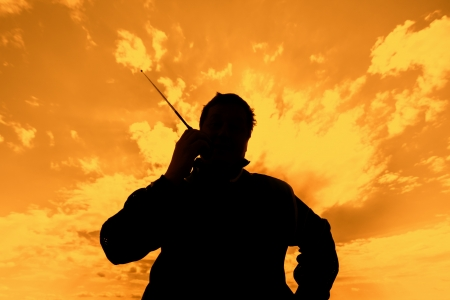 concatenation: Silhouette of the man with a portable radio set against the sunset sky Stock Photo