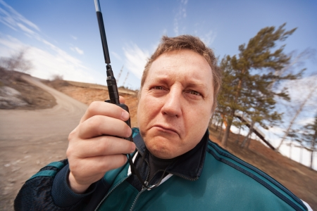 catenation: Amusing portrait of the serious man with a  portable radio set in a hand on outdoors Stock Photo