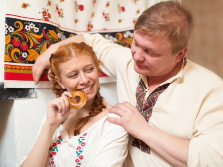 couple in national costume  near Russian stove photo