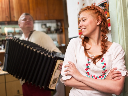 courting: The girl  near Russian stove  and  guy with an accordion