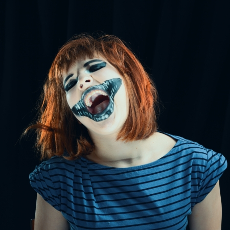 Portrait of the red-haired girl makeup up for celebrating  Halloween, on a black background