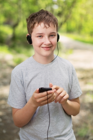 The boy in headphones listens to music in park photo