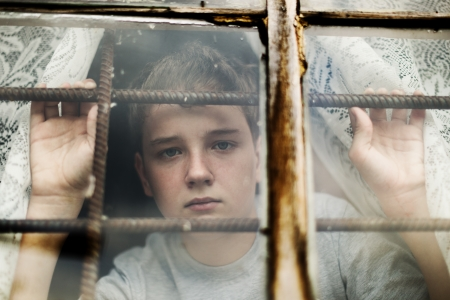 gente pobre: El ni�o es triste mira por la ventana a trav�s de una red Foto de archivo