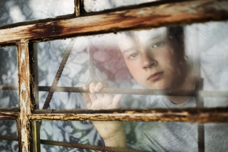 The boy it is sad looks out of the window through a lattice photo