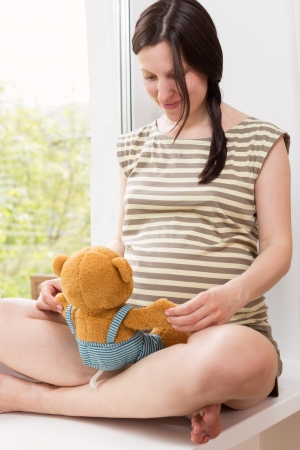 Pregnant woman sitting at home on the windowsill