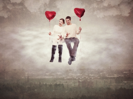 Young couple enamoured, flying over a city on a cloud