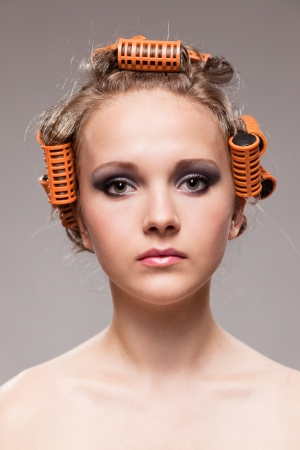 Stylish girl portrait with fashion makeup and hair curlers, isolated on grey background, hair and beauty treatment concept