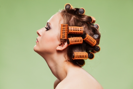 Stylish girl portrait with fashion makeup and hair curlers, isolated on green background, hair and beauty treatment concept  photo