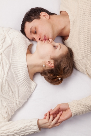 girl and the young man in white knitted jackets lie on a sofa photo