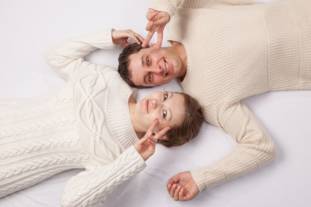 girl and the young man in white knitted jackets lie on a sofa Stock Photo