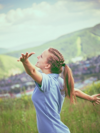 Happy and beautiful young girl  in a summer field