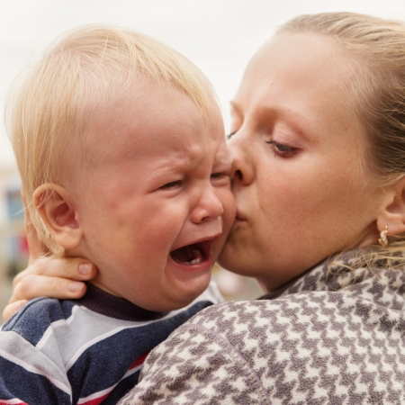 Portrait of a crying little boy who is being held by her mother , outdoors
