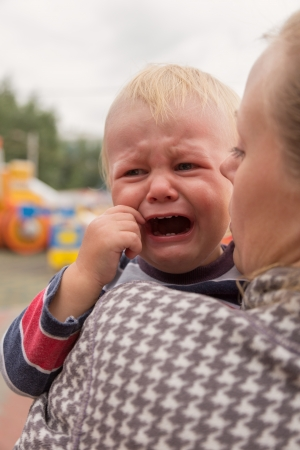 Portrait of a crying little boy who is being held by her mother , outdoors photo