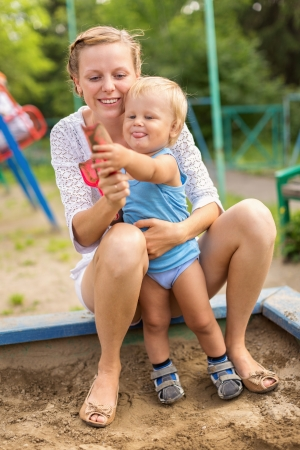 Mother and baby boy playing in the sandbox  photo
