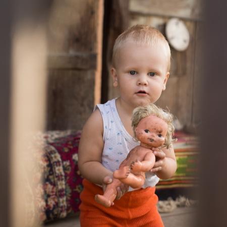 Malý chlapec si hraje s panenkou dům veranda